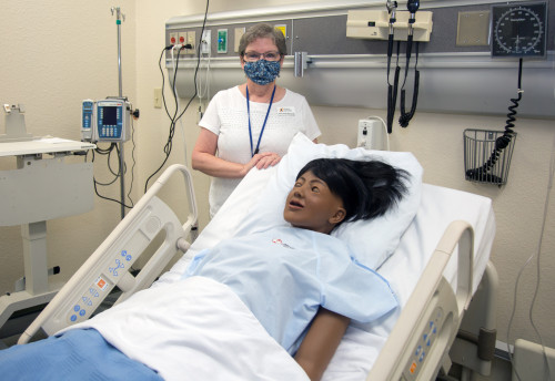Nancy Eaton, simulation coordinator for the Nursing program, stands with one of the new Advanced ...
