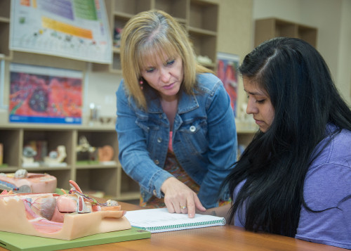 Nursing graduate Doris Dlouhy helps Cecily Gonzales with homework for her Anatomy and Physiology ...